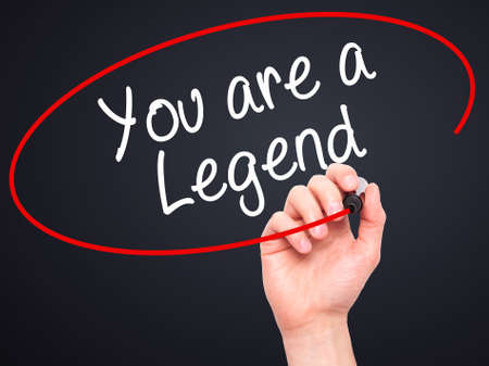 legend: Man Hand writing You are a Legend   with black marker on visual screen. Isolated on background. Business, technology, internet concept. Stock Photo