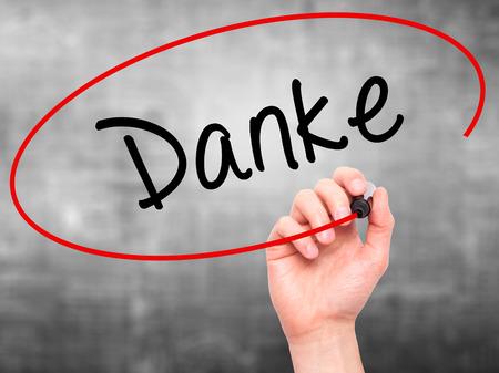 agradecimiento: Hombre de la mano con marcador escribiendo Danke a bordo transparente limpie. Aislado en gris. Negocios, internet, concepto de la tecnología. Foto de stock