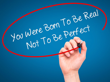 true born: Man Hand writing You Were Born To Be Real Not To Be Perfect with black marker on visual screen. Isolated on blue. Business, technology, internet concept.