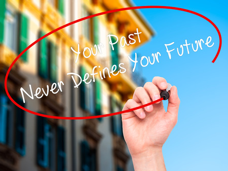 defines: Man Hand writing Your Past Never Defines Your Future with black marker on visual screen. Isolated on city. Business, technology, internet concept. Stock Photo