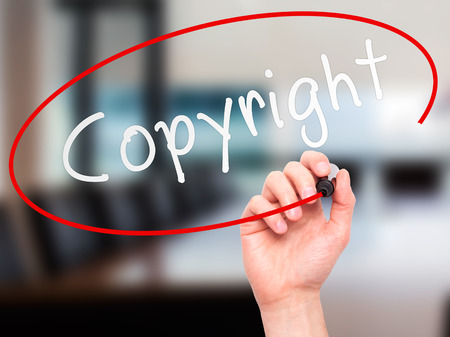 Man hand writing Copyright on visual screen. Business,help, internet, technology concept. Isolated on office. Stock Photo