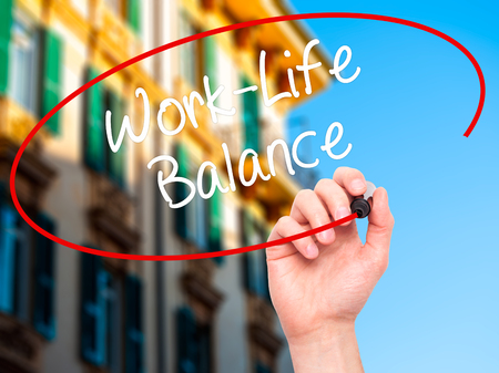 health equity: Man Hand writing Work-Life Balance with black marker on visual screen. Isolated on city. Business, technology, internet concept. Stock Photo