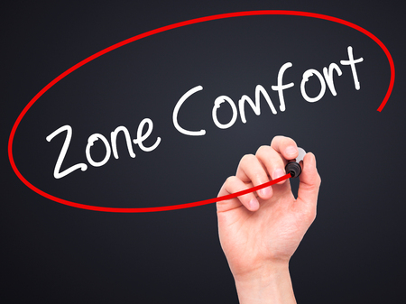 quo: Man Hand writing Zone Comfort with black marker on visual screen. Isolated on black. Business,  internet concept. Stock Photo