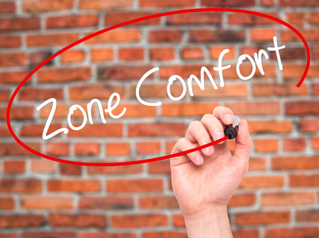 Man Hand writing Zone Comfort with black marker on visual screen. Isolated on bricks. Business,  internet concept. Stock Photo
