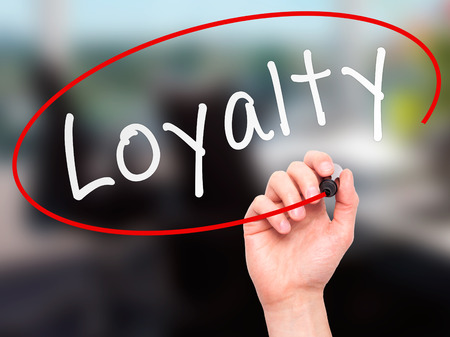 believable: Man Hand writing Loyalty with marker on transparent wipe board. Isolated on office. Business, internet, technology concept.  Stock Photo