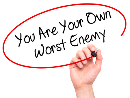 the worst: Man Hand writing You Are Your Own Worst Enemy with black marker on visual screen. Isolated on background. Business, technology, internet concept. Stock Photo