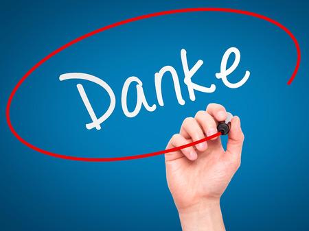 agradecimiento: Hombre de la mano con marcador escribiendo Danke a bordo transparente limpie. Aislado en azul. Negocios, internet, concepto de la tecnología. Foto de stock