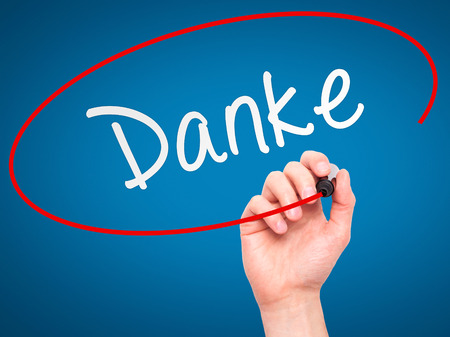 dank: Man Hand writing Danke with marker on transparent wipe board. Isolated on blue. Business, internet, technology concept. Stock Photo