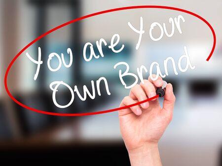 Escritura de la mano del hombre Usted es su propia marca con el marcador negro en la pantalla visual. Aislado en la oficina. Foto de archivo