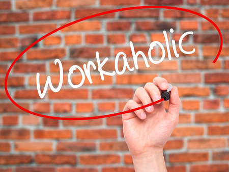 workaholic: Man Hand writing Workaholic with black marker on visual screen. Isolated on bricks. Stock Photo