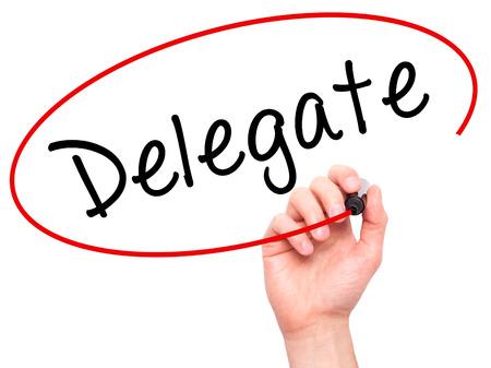 delegar: Hombre de la mano escribiendo Delegado marcador negro en la pantalla visual. Aislado en blanco. Negocios, la tecnología, el concepto de internet. imagen de archivo