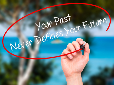 defines: Man Hand writing Your Past Never Defines Your Future with black marker on visual screen. Isolated on nature. Business, technology, internet concept. Stock Photo