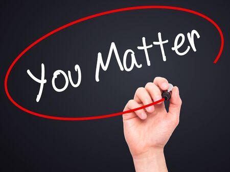 business matter: Man Hand writing You Matter with black marker on visual screen. Isolated on black. Business, technology, internet concept. Stock Photo Stock Photo