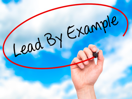 Man Hand writing Lead By Example with marker on transparent wipe board. Isolated on sky. Business, internet, technology concept. Stock Photo