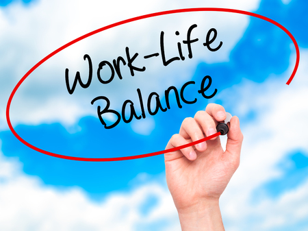 health equity: Man Hand writing Work-Life Balance with black marker on visual screen. Isolated on sky. Business, technology, internet concept. Stock Photo