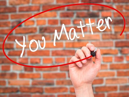 business matter: Man Hand writing You Matter with black marker on visual screen. Isolated on bricks. Business, technology, internet concept. Stock Photo Stock Photo