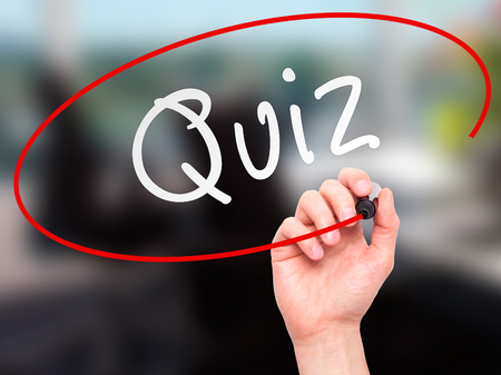 Man Hand writing Quiz with marker on transparent wipe board. Isolated on office. Business, internet, technology concept.  Stock Photo