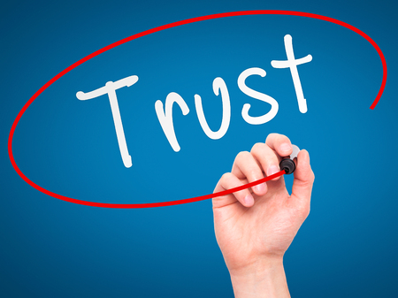 believable: Man Hand writing Trust black marker on visual screen. Isolated on blue. Business, technology, internet concept. Stock Image