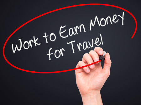 earn money: Man Hand writing Work to Earn Money for Travel with black marker on visual screen. Isolated on black. Business, technology, internet concept. Stock Photo Stock Photo