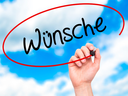 to acclaim: Man Hand writing Wunsche (Wishes in German) with black marker on visual screen. Isolated on background. Business, technology, internet concept. Stock Photo