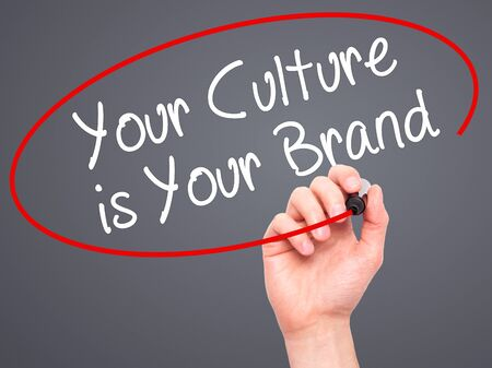 identidad cultural: Man Hand writing Your Culture is Your Brand with black marker on visual screen. Isolated on grey. Business, technology, internet concept. Stock Photo