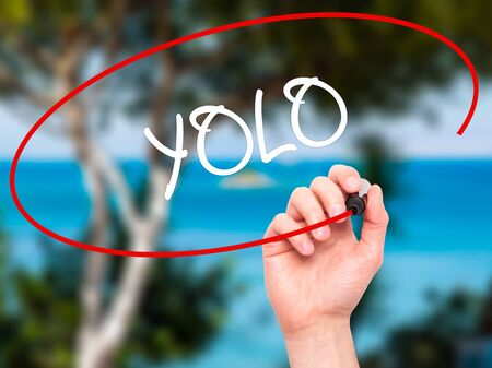 once person: Man Hand writing YOLO (You Only Live Once) with black marker on visual screen. Isolated on nature. Business, technology, internet concept. Stock Photo