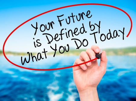defined: Man Hand writing Your Future is Defined by What You Do Today with black marker on visual screen. Isolated on nature. Stock Photo