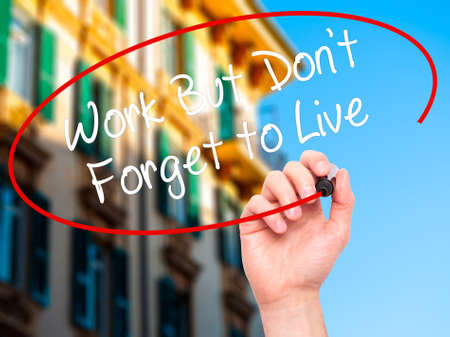 live work city: Man Hand writing Work But Dont Forget to Live  with black marker on visual screen. Isolated on city. Business, technology, internet concept. Stock Photo
