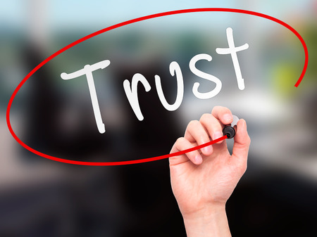 believable: Man Hand writing Trust black marker on visual screen. Isolated on office. Business, technology, internet concept. Stock Image Stock Photo