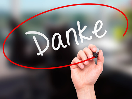 dank: Man Hand writing Danke with marker on transparent wipe board. Isolated on office. Business, internet, technology concept. Stock Photo