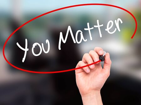 business matter: Man Hand writing You Matter with black marker on visual screen. Isolated on office. Business, technology, internet concept. Stock Photo