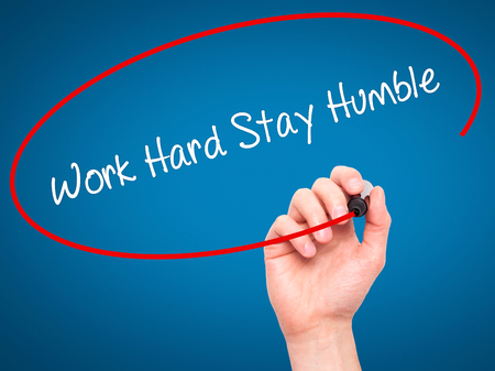 modesty: Man Hand writing Work Hard Stay Humble  with black marker on visual screen. Isolated on blue. Business, technology, internet concept. Stock Photo