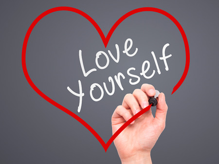 egoistic: Man Hand writing Love Yourself with marker on transparent wipe board, inside heart shape. Isolated on grey. Business, internet, technology concept. Stock Photo