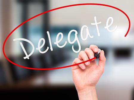 delegar: Hombre de la mano escribiendo Delegado marcador negro en la pantalla visual. Aislado en la oficina. Negocios, la tecnolog�a, el concepto de internet. imagen de archivo