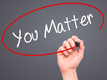 business matter: Man Hand writing You Matter with black marker on visual screen. Isolated on grey. Business, technology, internet concept. Stock Photo