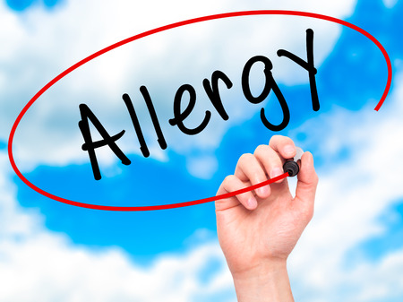 hypersensitivity: Man Hand writing Allergy with marker on transparent wipe board. Isolated on sky. Business, internet, technology concept. Stock Photo