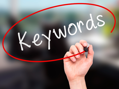 meta tags: Man hand writing Keywords on visual screen. Business,help, internet, technology concept. Isolated on office. Stock Photo Stock Photo