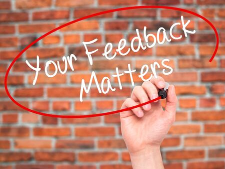 soliciting: Man Hand writing Your Feedback Matters with black marker on visual screen. Isolated on bricks. Business, technology, internet concept. Stock Photo