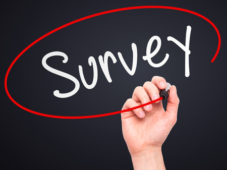 appraise: Man Hand writing Survey with marker on transparent wipe board isolated on black. Business, internet, technology concept. Stock Photo