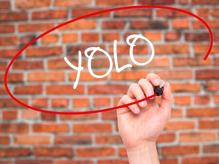 once person: Man Hand writing YOLO (You Only Live Once) with black marker on visual screen. Isolated on bricks. Business, technology, internet concept. Stock Photo