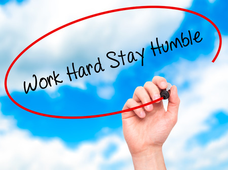 Man Hand writing Work Hard Stay Humble  with black marker on visual screen. Isolated on sky. Business, technology, internet concept.