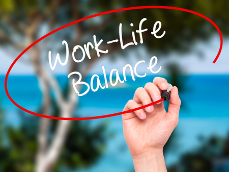 health equity: Man Hand writing Work-Life Balance with black marker on visual screen. Isolated on nature. Business, technology, internet concept. Stock Photo