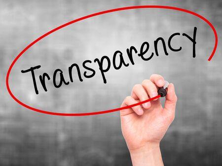 Man Hand writing Transparency with marker on transparent wipe board. Isolated on grey. Business, internet, technology concept. Stock Photo