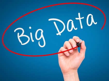 Man Hand writing Big Data with marker on transparent wipe board. Isolated on blue. Business, internet, technology concept. Stock Photo