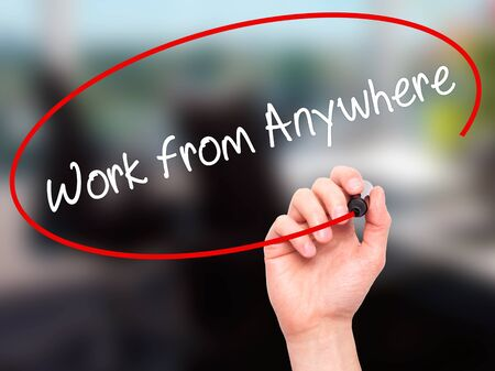 anywhere: Man Hand writing Work from Anywhere with black marker on visual screen. Isolated on office. Business, technology, internet concept. Stock Photo