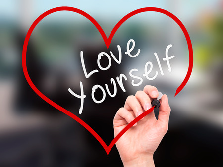 Man Hand writing Love Yourself with marker on transparent wipe board, inside heart shape. Isolated on office. Business, internet, technology concept. Stock Photo Stockfoto