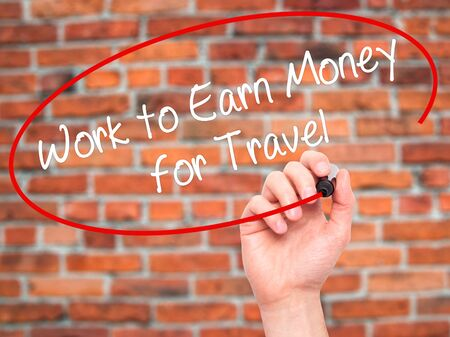 earn money: Man Hand writing Work to Earn Money for Travel with black marker on visual screen. Isolated on bricks. Business, technology, internet concept. Stock Photo