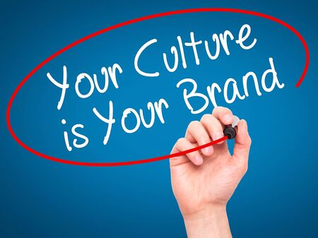 beliefs: Man Hand writing Your Culture is Your Brand with black marker on visual screen. Isolated on blue. Business, technology, internet concept. Stock Photo