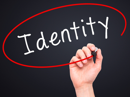 distinction: Man Hand writing Identity with black marker on visual screen. Isolated on black. Business, technology, internet concept. Stock Image Stock Photo