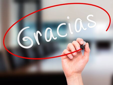 Man Hand writing Gracias with marker on transparent wipe board. Isolated on office. Business, internet, technology concept. Stock Photo